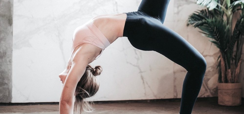 A woman in a backbend doing a full wheel yoga pose