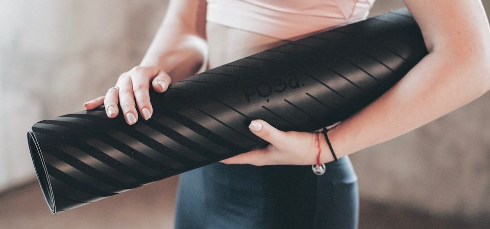 A woman holding a rolled up yoga mat