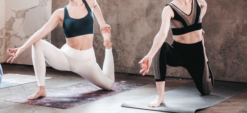 Two women on yoga mats doing a yoga pose